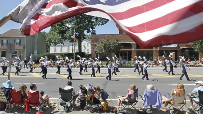 Under the colors of the American flag blowing in the wind, the Webster Marching Band performs for the hundreds that line the parade route at last year's annual Independence Day Parade in the village of Penfield.