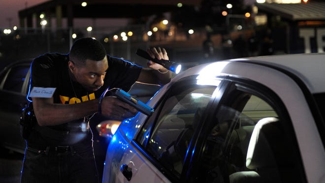 TSU student Mark Clear Jr. approaches a car cautiously during the city's first-ever Collegiate Citizen Police Academy. The students get hands-on experience of what it's like to be on the police force.