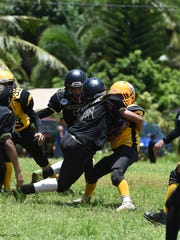 Saints player Dylan Peter Manibusan (6) makes the tackle against an Eagles player during their Triple J Ford GNYFF Youth Football League game at Eagle Field in Mangilao on Aug. 30.