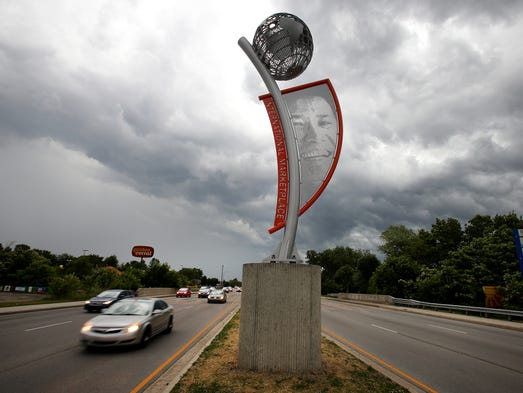 Motorists pass a new sculpture that was unveiled for the International Marketplace on W. 38th Street near High School Road, Wednesday, June 18, 2014, in Indianapolis. The new marketing effort aims to publicize the diversity of the area.