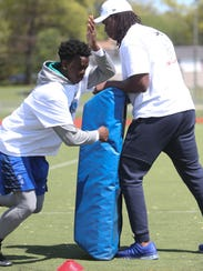 Lions defensive end Ziggy Ansah works with Mark Lewis