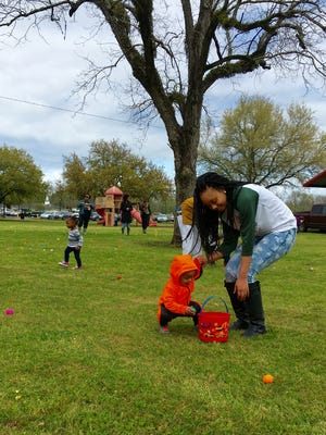 Erica Bell helps son Promise Whitlock, 1, collect eggs Thursday at an Easter egg hunt at Frank O. Hunter Park in Alexandria.