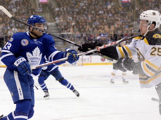 Toronto Maple Leafs center Nazem Kadri (43) and Boston Bruins defenseman Brandon Carlo (25) clash with high sticks during the second period of an NHL hockey game in Toronto, Friday, Nov. 10, 2017. Only Carlo was penalized on the play(Nathan Denette/The Canadian Press via AP)