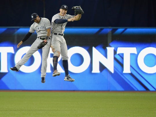 New York Yankees center fielder Aaron Hicks, left, and right fielder Aaron Judge celebrate after defeating the Toronto Blue Jays in a baseball game in Toronto on Thursday, March 29, 2018. (Nathan Denette/The Canadian Press via AP)