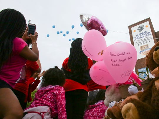Balloons are released in honor of Amy Inita Joyner-Francis during a gathering of mourners Friday following her beating death at Howard High School of Technology Thursday.