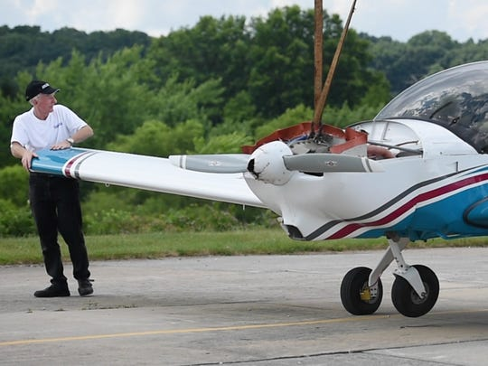 Pilot Lawrence Nolte, left, walks with his plane as it is towed back to a hangar.