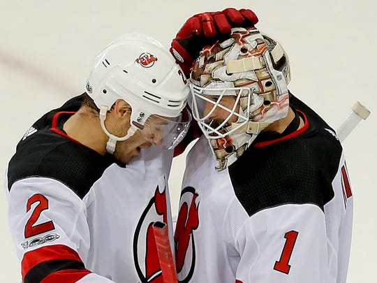 New Jersey Devils defenseman John Moore (2) celebrates with goalie Keith Kinkaid (1) after the Devils beat the New York Rangers 3-2 in an NHL hockey game game, Saturday, Oct. 14, 2017, in New York. (AP Photo/Julie Jacobson)
