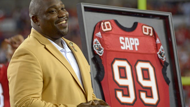 FILE - In this Nov. 11, 2013, file photo, former Tampa Bay Buccaneers player Warren Sapp smiles after being inducted in the Ring of Honor ceremony during halftime in an NFL football game between the Tampa Bay Buccaneers and the Miami Dolphins in Tampa, Fla. Sapp was bitten by a shark during a fishing trip off the Florida Keys on Wednesday, July 27, 2016.