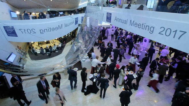 Participants talk on the fourth day of the annual meeting of the World Economic Forum in Davos, Switzerland, on Friday.
