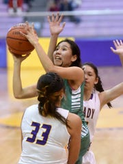 Farmington senior Meeya Yazzie attempts a shot on Saturday against Kirtland Central at Bronco Arena in Kirtland.