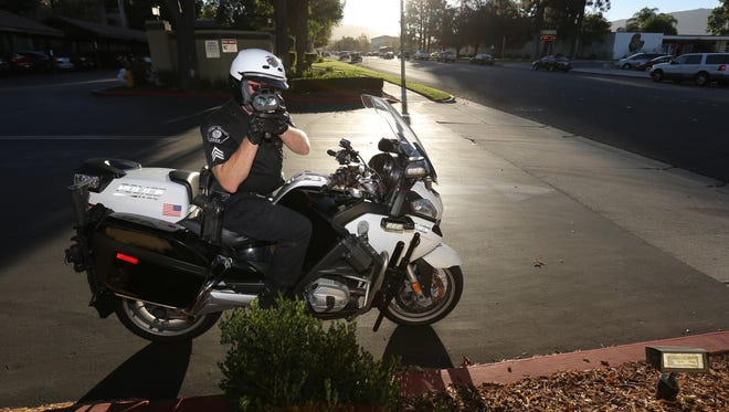 Police Sgt. Billy Lappin uses radar to monitor traffic in front of Simi Valley High School during a morning crackdown on speeders.