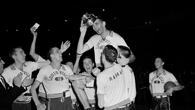 Louisville's Charlie Tyra, carried by his happy teammates, places the NIT's most valuable player award on his head after presentation at New York's Madison Square Garden, March 24, 1956. Tyra, who scored 27 points and outplayed his bigger opponent, Bill Uhl, led the Louisville quintet to victory over the favored Dayton Flyers in the title came, 93-80. Other identifiable players are Al Glaza (16) and Herb Harrah (second from right in foreground. (AP Photo/John Rooney)