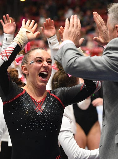 Southern Utah University sophomore Madison Mcbride celebrates with her team during competition against Utah State University at the America First Center Friday, February 12, 2018.