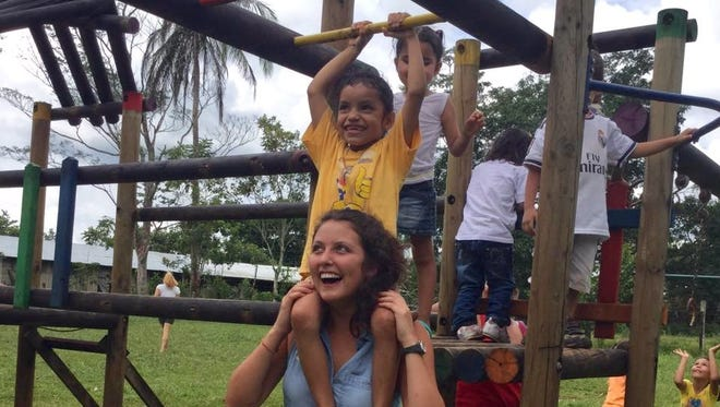 Malory Sanvidge of Oshkosh plays with children during an 11-month mission trip to 11 countries.