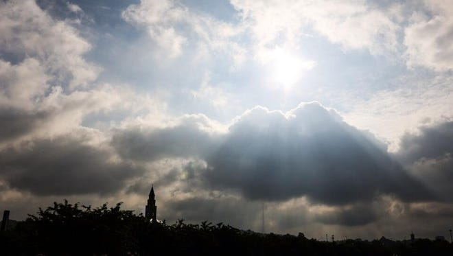 Sun breaks through cloudy sky over downtown Cincinnati on Thursday morning.