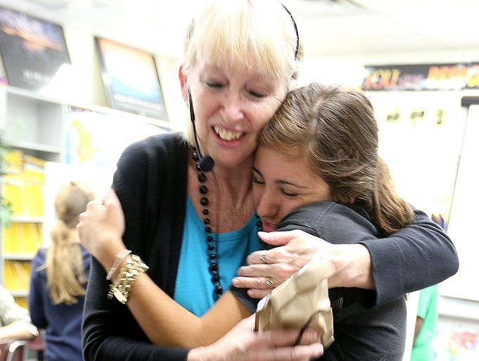 Teacher BJ Wise hugs Lincoln senior Darya Massoudi. Lincoln Trojan seniors started a tradition of giving back. On May 20 they are no longer required to be at school. They are calling the day Ògive back dayÓ and are using the time to thank those who made a difference in their lives. They teachers at Swift Creek Middle School where they have fond memories from attending.