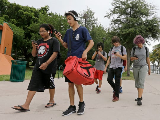 """A group of Pokemon Go players check their smartphones as they look for Pokemon, Tuesday, July 12, 2016, at Bayfront Park in downtown Miami. The Pokemon Go craze has sent legions of players hiking around cities and battling with """"pocket monsters"""" on their smartphones."""