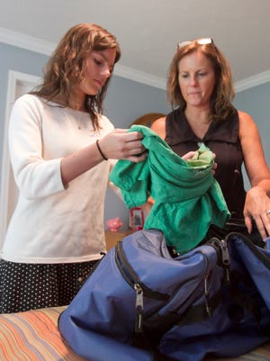 Genoa Township resident Kaeleigh Heatley packs a T-shirt that will help identify her with a group of people participating in a three-month volunteer effort in Asia, assisted in her packing by her mother, Andrea Campbell.