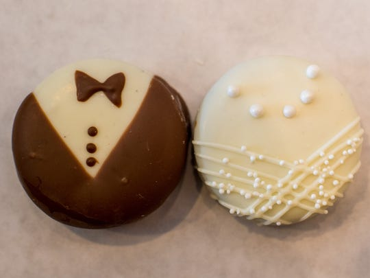 Groom and bride chocolate-covered Oreos are among wedding-themed items are sold at Lolli's Chocolates.