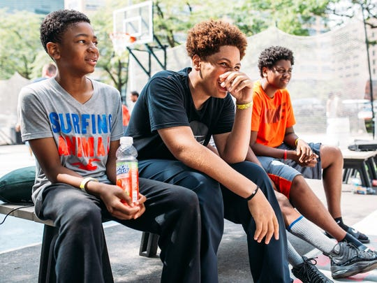Karon Wilks, 14, of Detroit, Christopher Freeman, 15, of Detroit, and Sumari McCullough, 16, of Detroit spectate and laugh at the ongoing game on the basketball courts at Campus Martius in downtown Detroit on Friday, July 17, 2015.