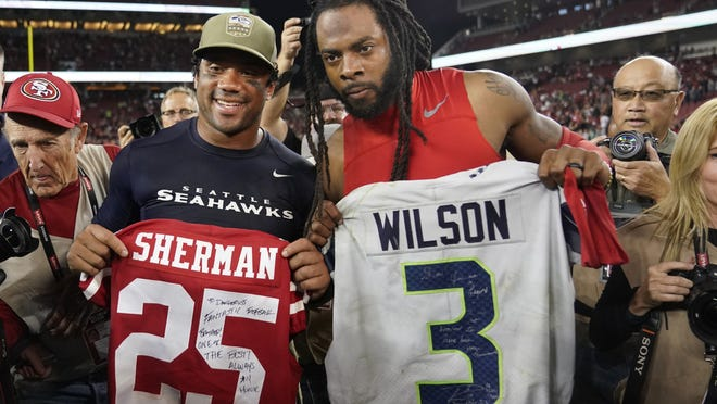 Seattle Seahawks quarterback Russell Wilson, left, exchanges jerseys with San Francisco 49ers cornerback Richard Sherman after a game last season. NFL teams will be prohibited from postgame interactions within 6 feet of each other, so players won't be allowed to exchange jerseys after games as part of the guidelines to help limit the spread of the coronavirus.