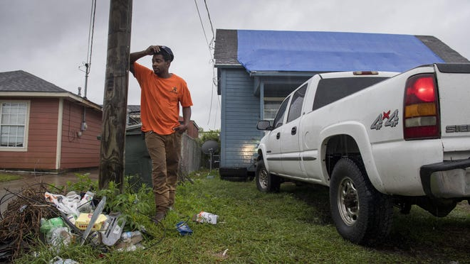 Standing in front of his house covered in a blue tarp from Hurricane Laura damage, Joshua Espree, 30, plans on staying in Lake Charles, La., and helping his family  as Hurricane Delta approaches the area  on Friday, Oct. 9, 2020.  Delta is expected to make landfall late Friday.