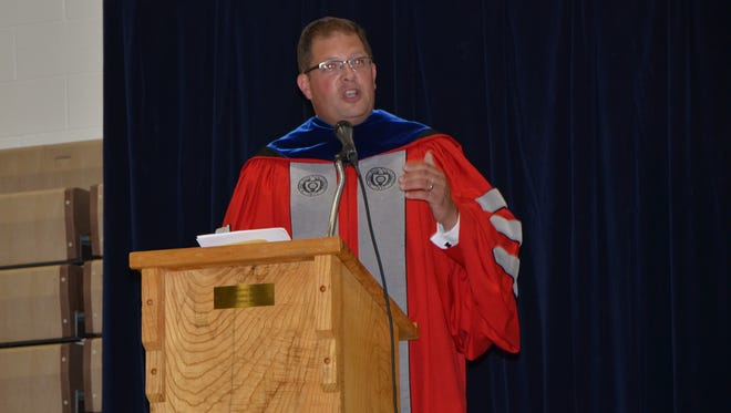 Woodmore High School graduate and Ohio State University band director Jonathan Waters speaks June 9 at graduation ceremonies there.