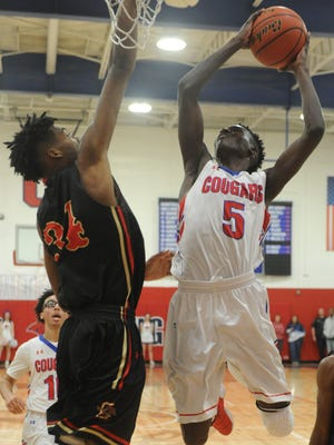 Cooper's Matthew Falade (5) drives to the basket as Lubbock Coronado's Bronzea Giddens defends. The Mustangs beat Cooper 77-56 in the District 4-5A game Friday, Jan. 19, 2018 at Cougar Gym.