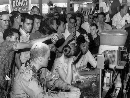 In this May 28, 1963, file photograph, a group of whites poured sugar, ketchup and mustard over the heads of Tougaloo College student demonstrators at a sit-in demonstration at a Woolworth's lunch counter in downtown Jackson, Miss.