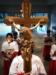 The Processional Cross holder waits at the back of