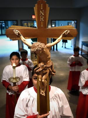 The Processional Cross holder waits at the back of the sanctuary for the start of mass for the Sagrado Corazon congregation on Oct. 2, 2016.