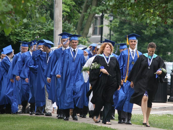 Highlands High School Class of 2014 senior sponsor teachers Kim Grillot, left, and Jennifer Nash, lead valedictorian Luke Brockett and other graduates across campus to commencement ceremonies inside the school's Performing Arts Center June 8.