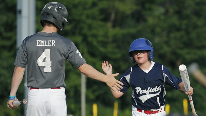 Dylan Emler high-fives bat boy D.J. Teeter after picking up a bat for the Penfield Little League Junior Team at Bachman Field at the Penfield Town Hall. The team is headed for the state tournament.