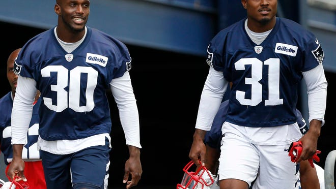 Patriots cornerback Jason McCourty, left, heads out to the practice field last year with one of his protégés, cornerback Jonathan Jones.