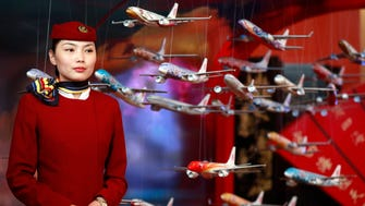 In this file photo from June 12, 2012, an Air China flight attendant stands near model planes at the International Air Transport Association (IATA) 68th Annual General Meeting (AGM) and World Air Transport Summit in Beijing.