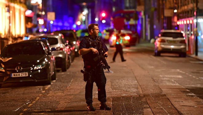 An armed policeman stands on Borough High Street as police are dealing with an incident on London Bridge in London on June 3.