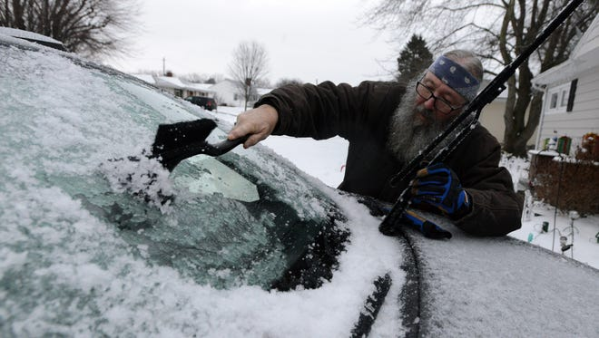 John Pupek scrapes the ice off the windshield of his wife's vehicle Monday morning, Jan. 8, 2018, on Wetsell Avenue in Lancaster. An early morning winter storm dropped a mix of rain, sleet, snow and ice on the area, coating vehicles and roads with a slick layer of ice and slush.