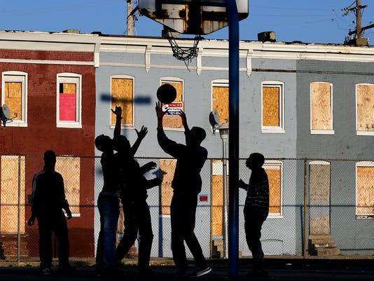 Young men play basketball at a Baltimore playground.