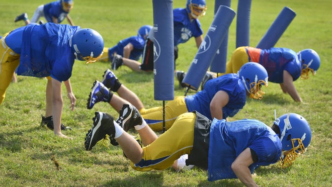 Kimball football players drop to the ground and back up during conditioning exercises in practice Monday at the school.
