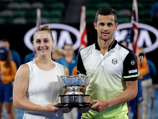 Canada's Gabriela Dabrowski, left, and Croatia's Mate Pavic hold their trophy aloft after defeating Hungary's Timea Babos and partner India's Rohan Bopanna in the mixed doubles final at the Australian Open tennis championships in Melbourne, Australia, Sunday, Jan. 28, 2018. (AP Photo/Dita Alangkara)