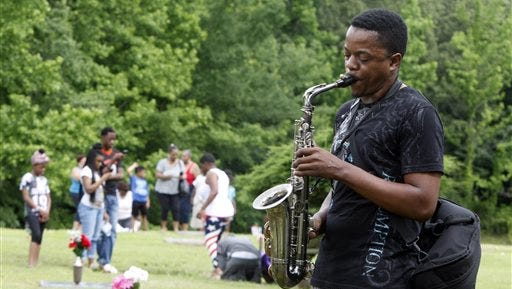 """Darnell Bonner plays """"Amazing Grace"""" during a memorial ceremony at Galilee Memorial Gardens cemetery Monday, May 25, 2015, in Memphis, Tenn. The cemetery was opened to visitors on Memorial Day after being closed after the cemetery owner was accused of burying multiple bodies in single graves by crushing and stacking caskets. (AP Photo/Karen Pulfer Focht)"""