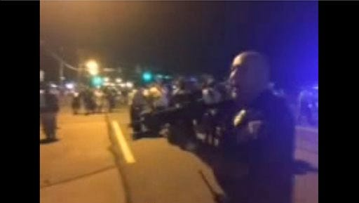 This image taken from video shows apolice officer who was part of the effort to keep peace during protests in Ferguson pointing a semi-automatic assault rifle at demonstrators Tuesday.