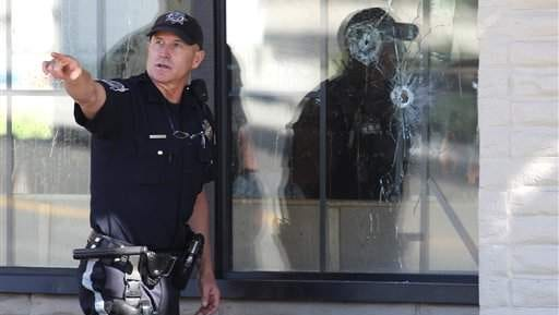 With bullet holes seen in a window, officers look for evidence at the scene of a shooting at an IHOP restaurant in Carson City, Nev. on Tuesday, Sept. 6, 2011. Seven people were wounded after a gunman opened fire at the restaurant, authorities said.