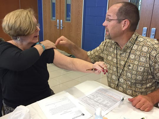 Mary Rogers, Waynesboro, rolls up her sleeve to get ready for a vaccine for whooping cough during a clinic Friday, November 11, 2016 at Chambersburg Area Senior High School. The Pa. Dept. of Health hosted the clinic after outbreaks in the area. Fred Oberholtzer, R.N. administered the shot.