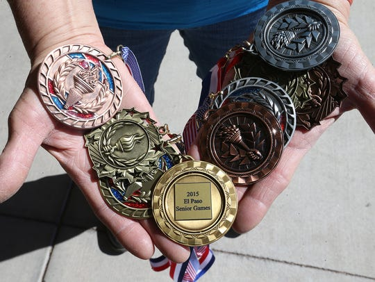 Cathy Soto shows a number medals she has won in past