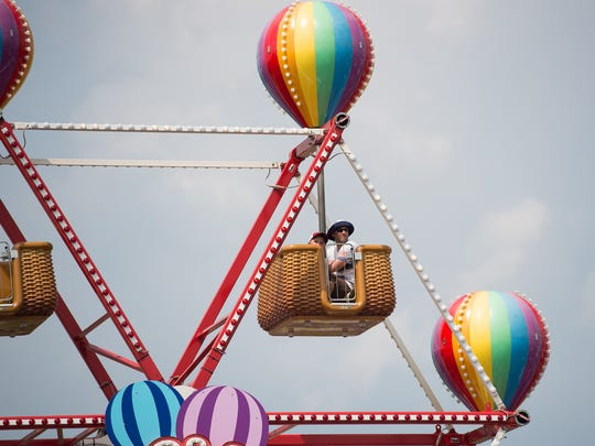 Jason Schoenkopf and his son Jack (6) of Verona, N.J., ride the Balloon Fiesta ride during the Delaware State Fair.