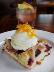 """Goodkind, a shareable plates restaurant, incorporates seasonal produce into its savory and sweet dishes, as in this plum foccacia dessert. In the background, the """"As It Lies"""" cocktail made with Cynar, lemon and black cherry iced tea. Goodkind restaurant and tavern is in Milwaukee's Bay View neighborhood."""