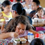 Children eat a free lunch at youth program in Phoenix on July 22, 2014.
