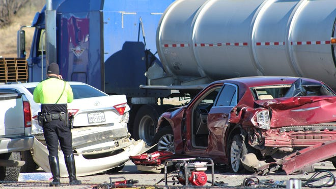 An Abilene Police Department officer photographs a crash scene at which six vehicles still were in place in the westbound lane of Interstate 20 on Friday morning. Fatalities and injuries were confirmed by APD.