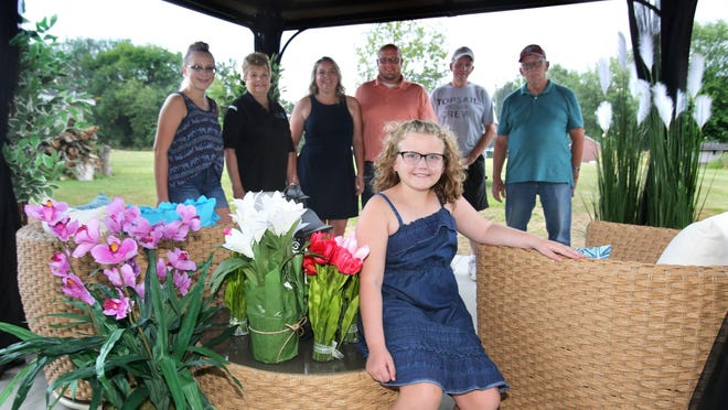 Gracie Andrews is shown in her new pergola in the backyard of her Osnaburg Township home. The structure was built for her and her family through the nonprofit Wishes Can Happen, which works with children with life-threatening illnesses. Behind her are (left to right): Natalie Andrews, Gracie's sister; Cyndi Morrow, executive director of Wishes Can Happen; Noel and Tim Andrews, Gracie's mother and father; and builders Ron Shackle and Dan St. Clair.